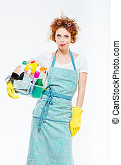 Irritated woman in yellow gloves holding box with cleansers...