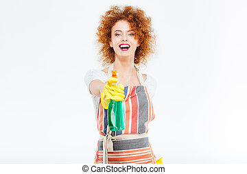 Cheerful woman in yellow gloves holding spray with liquid...