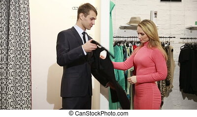 Male seller offers women dress blonde chooses clothes - Male...