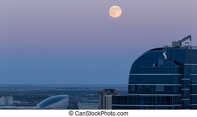 Nazarbayev Center and blue tower, after Sunset with full moon rising. Astana, Kazakhstan