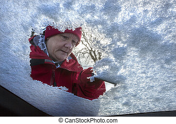 Driving - Winter Snow - Windshield - Senior woman clearing...