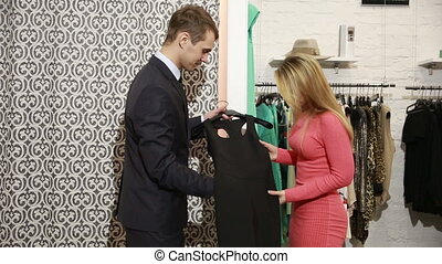 Male seller offers women dress. blonde chooses clothes