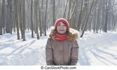 Happy young woman throws snow in park, slowmotion - Happy...