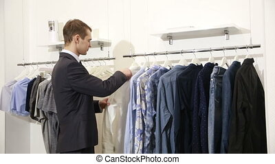 man chooses clothes in shop. man in a business suit looking shirt