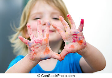 Cute preschooler girl with smile showing colored hands. Selective focus on palms
