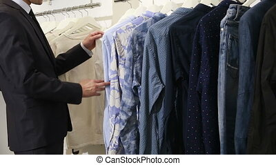 man chooses clothes in shop. man in a business suit looking...