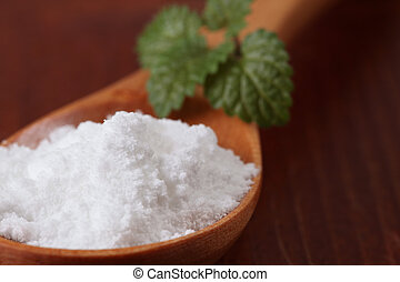 Icing sugar in a wooden spoon with fresh lemon balm leaf