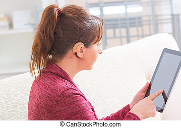 Deaf woman using tablet - Smiling Deaf woman using tablet at...