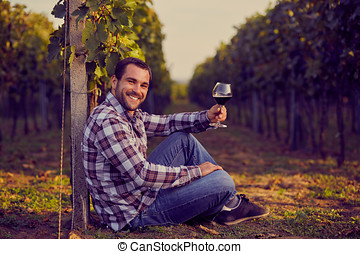 Winemaker siting in vineyard with a glass of red wine, toned