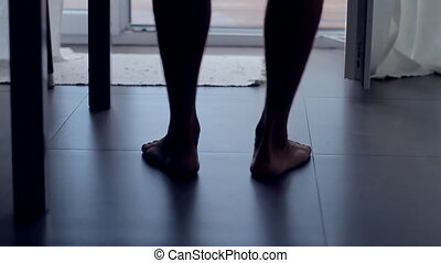 Feet of barefoot man comes out on the veranda in the summer,...