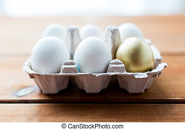 close up of white and gold eggs in egg box - easter, food,...