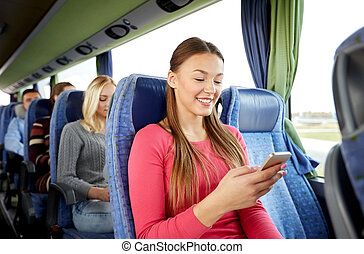 happy woman sitting in travel bus with smartphone -...