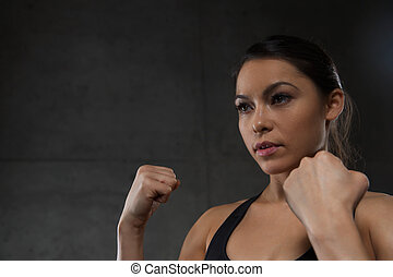 woman holding fists and fighting in gym - sport, fitness,...