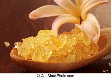 Yellow bath salt in a wooden spoon