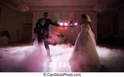 Beautiful newlywed couple first dance at reception, smoke...
