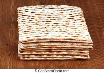 Matzah on wooden table which is the unleavened bread served...