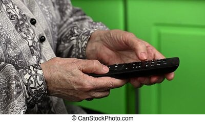 Old woman using tv remote control