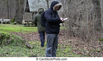 Ornithologists in the park with tablet PC and camcorder