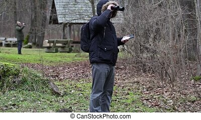 Ornithologists in the park with binoculars and camcorder