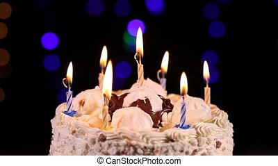 Birthday cake with burning candles rotating in front of...