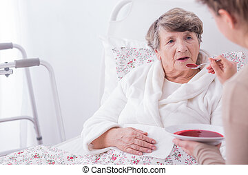 Woman eating dinner - Older sick woman eating dinner with...