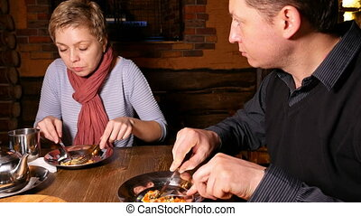 Young couple man and woman eating pizza in a cafe - Young...