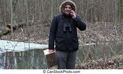 Ornithologist with smartphone and bird cage in the park near...