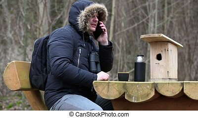 Ornithologist with smartphone near table
