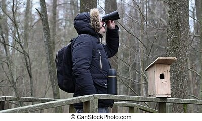Ornithologist with binoculars on the bridge near bird cage