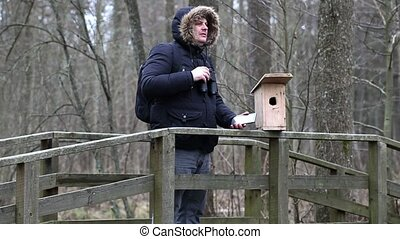 Ornithologist with binoculars and tablet PC near bird cage