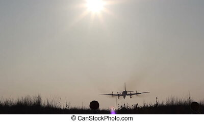 Landing large aircraft with four engines screw at sunset.