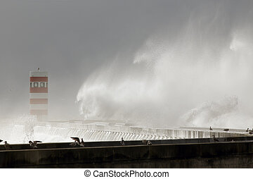 Winter seascape with stormy waves over pier and beacon in...