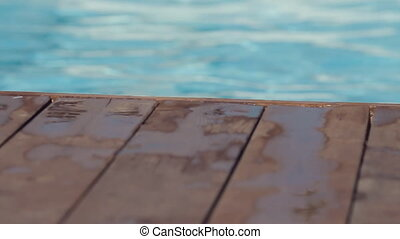 Man comes to edge of the pool on the wooden floor and dives into the water in slow motion