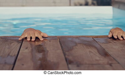 Muscular strong man resurfaces from a swimming pool in the summer