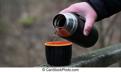 Man poured tea from thermos