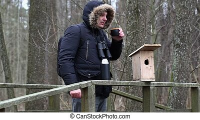 Ornithologist with binoculars drink tea on the bridge near...