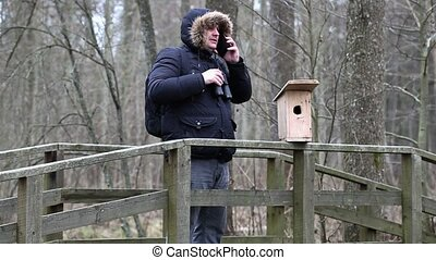 Ornithologist with binoculars and smartphone near bird cage