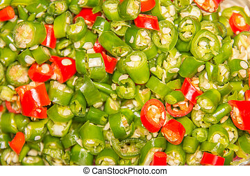 A pile of finely chopped chilli peppers on background