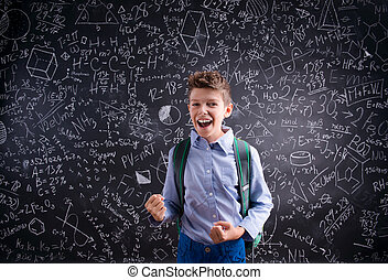 Excited and victorious boy against blackboard with...