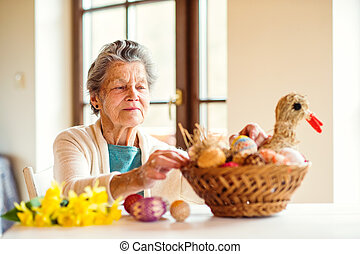Senior woman arranging basket with Easter eggs and daffodils...