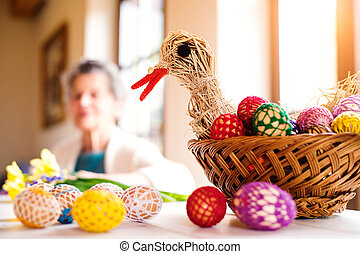 Basket with Easter eggs and hen in senior woman house -...
