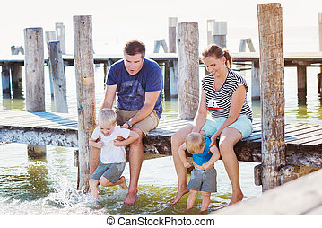 Family sitting on the pier, above water, sunny summer -...