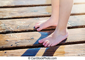 Detail of childs wet feet on pier, sunny summer day - Close...