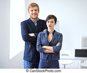 Businessman and businesswoman standing with crossed arms....