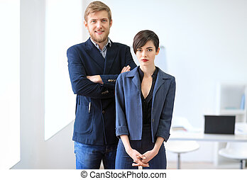Businessman and businesswoman standing in the office Team...