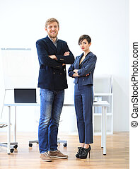 Businessman and businesswoman standing with crossed arms...