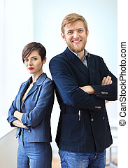 Businessman and businesswoman standing back to back with...