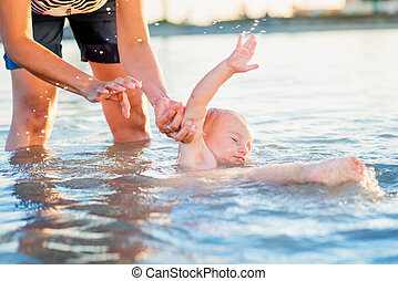 Little boy slipping accidentaly into water held by mother -...