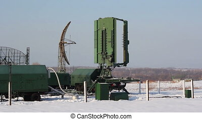 Green military radar station rotates in winter.