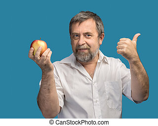 Smiling middle-aged man holding a red apple